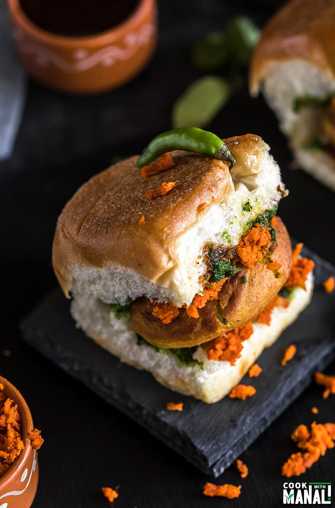 overhead shot of vada pav placed on a black coaster