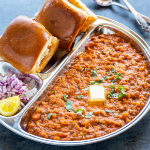 pav bhaji served in a steel plate with chopped onion and a pat of butter on top of bhaji