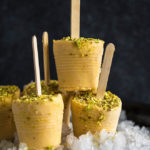 mango kulfi popsicles on top of crushed ice on a black plate