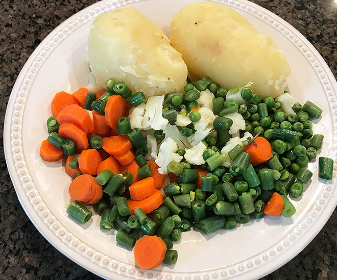 veggies and potatoes in a white plate