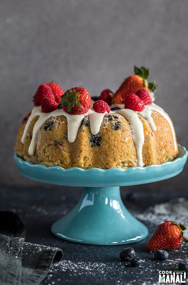 instant pot berry vanilla cake topped with fresh berries and placed on a blue cake stand