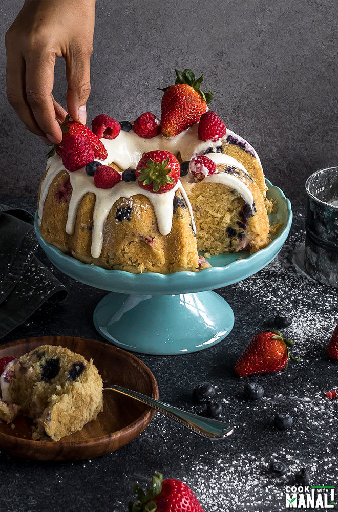 a hand placing a strawberry on a bundt cake placed on a blue cake stand