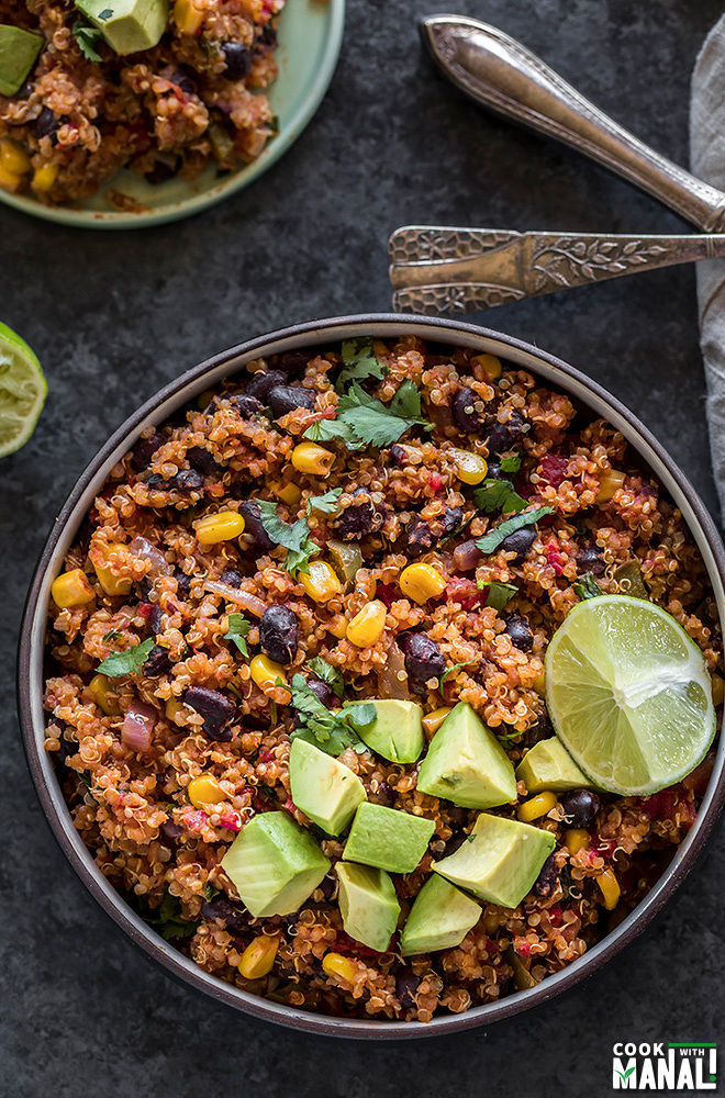 mexican quinoa in a round black bowl, garnished with diced avocados and a lime wedge
