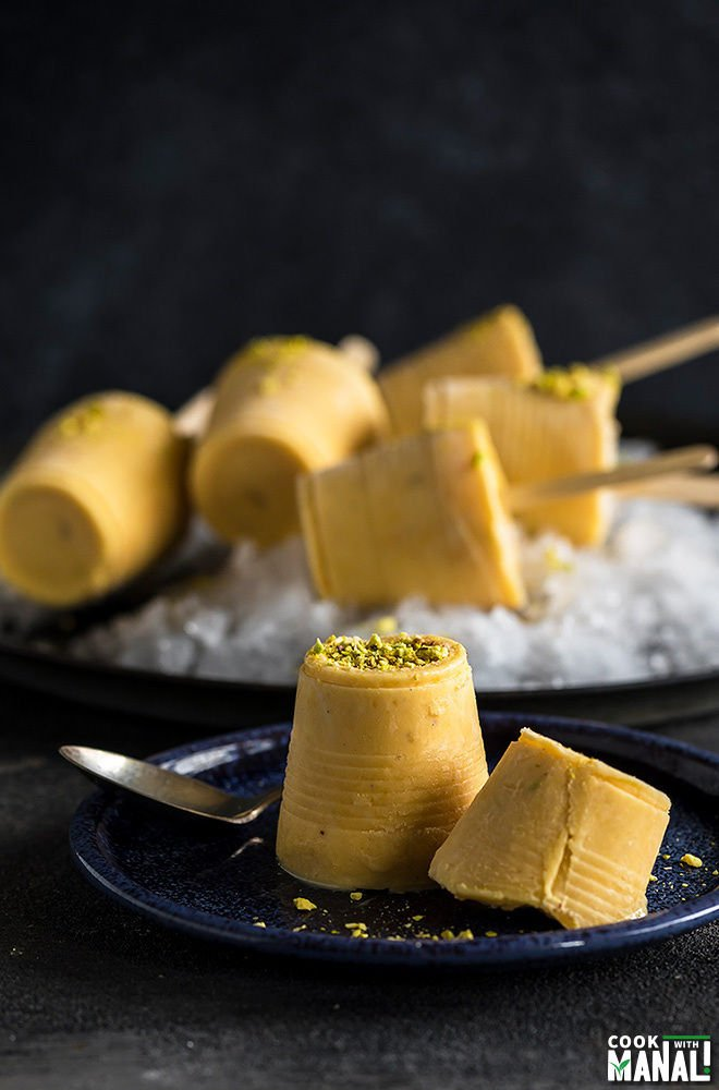 mango kulfi garnished with pisachios and served on a blue plate with more mango kulfi popsicles in the background