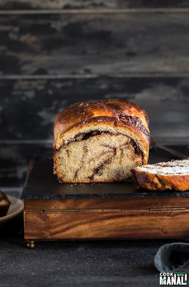 nutella babka served on a black cheese board with a cut slice on the side