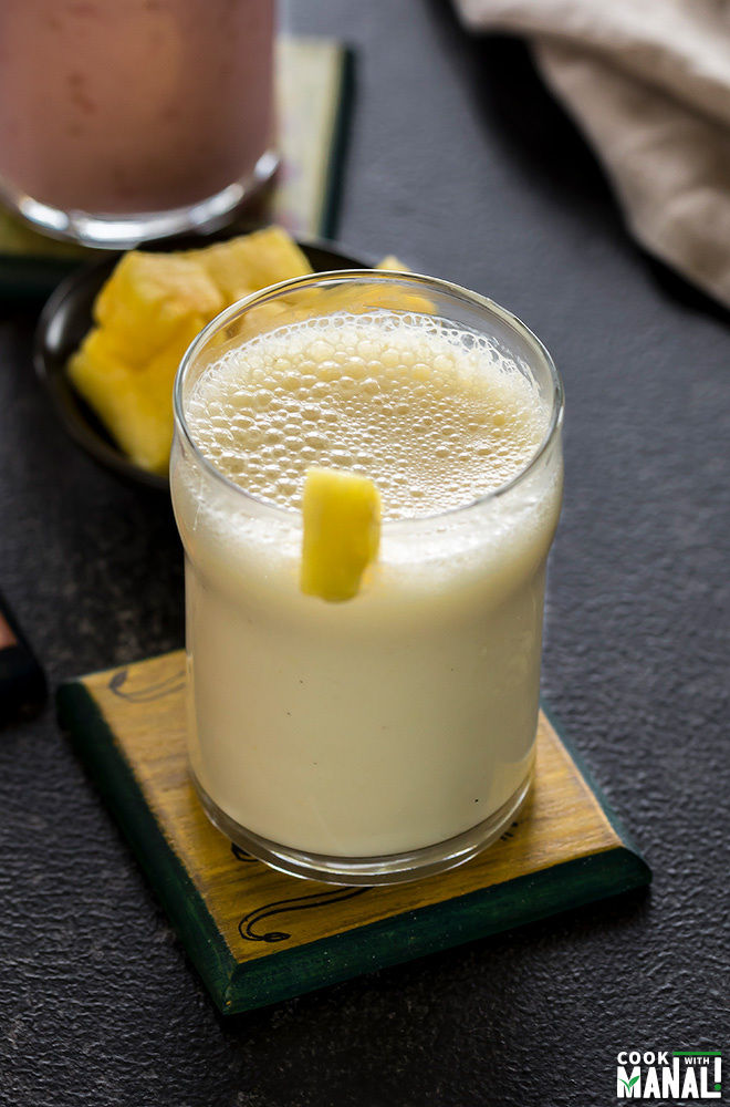 glass of pineapple ginger lassi on a coaster with more glasses of lassi in the background