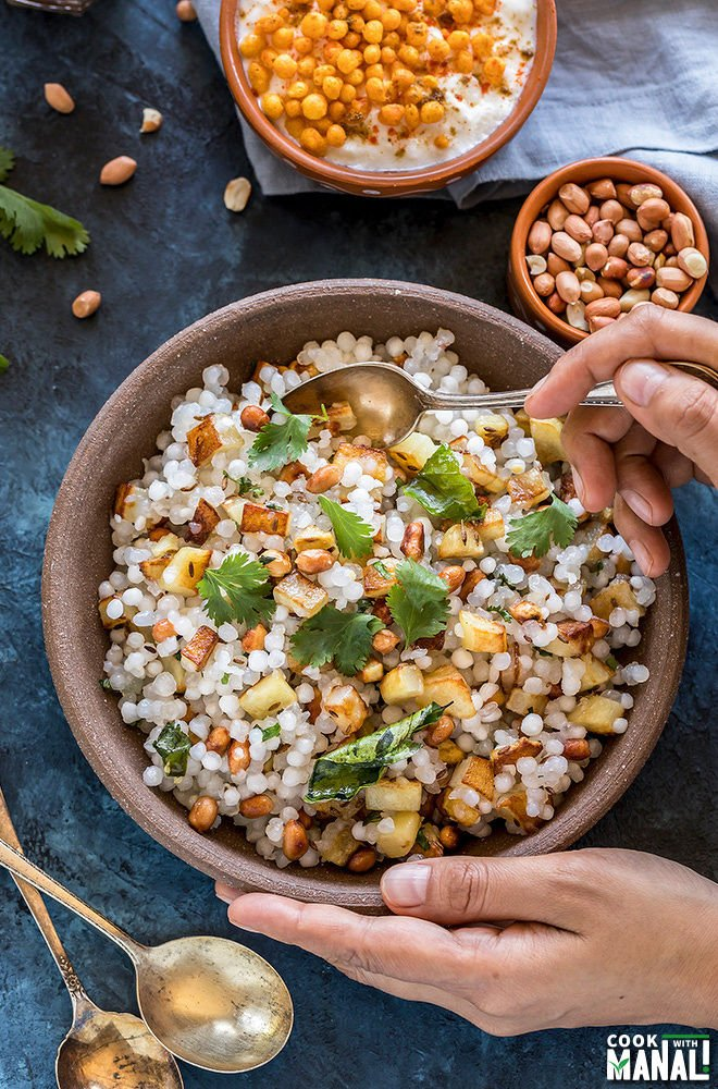 a pair of hands holding a bowl of sabudana khichdi served in a brown bowl