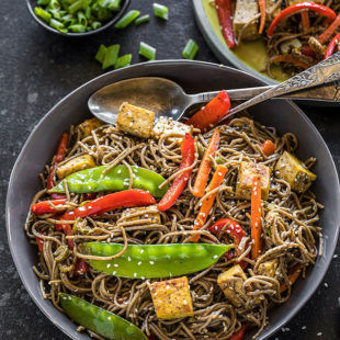 vegan soba noodles with carrots, snow peas, tofu, red pepper in a large grey bowl with a grey napkin on the side