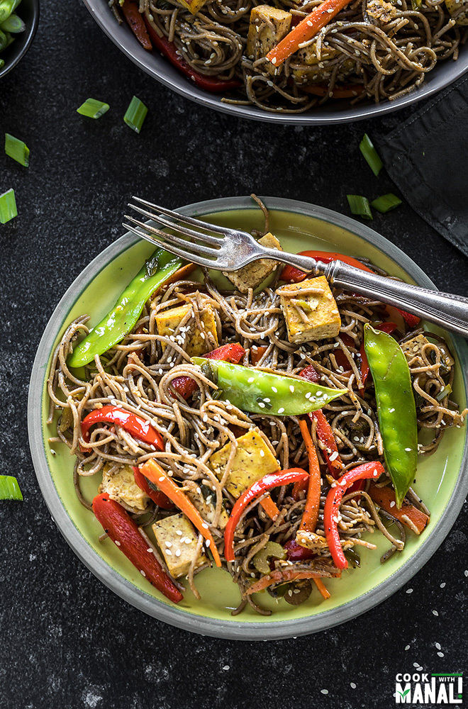 vegan soba noodles in a round yellow plate with a fork
