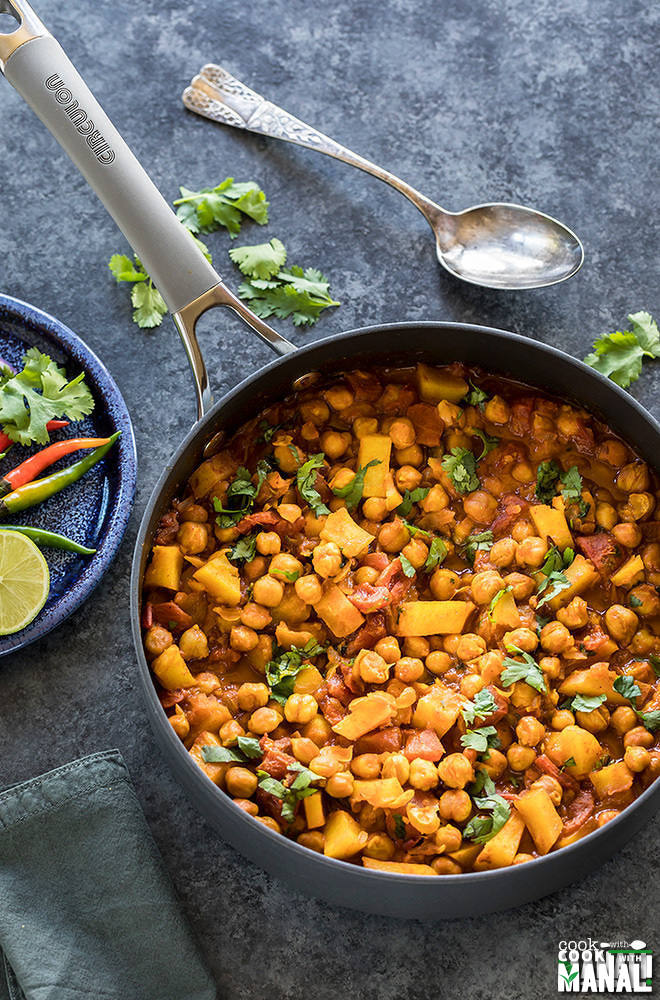 chana aloo served in a nonstick pan with a plate full of onions and chilies on the side