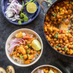 chana aloo served in 2 white bowls and topped with sliced onion and lime wedge