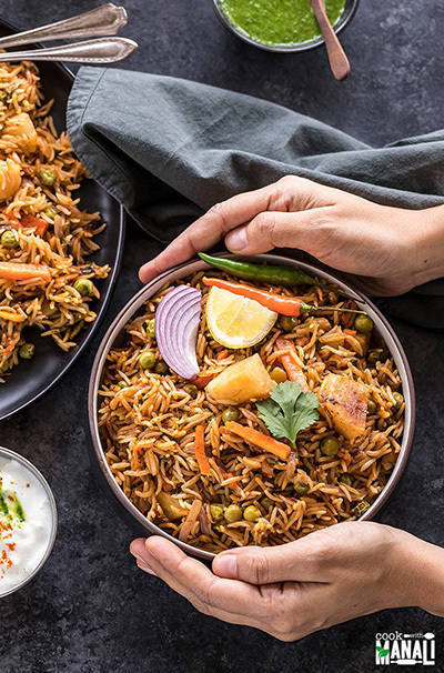 bowl of vegetable biryani held by a pair of hands