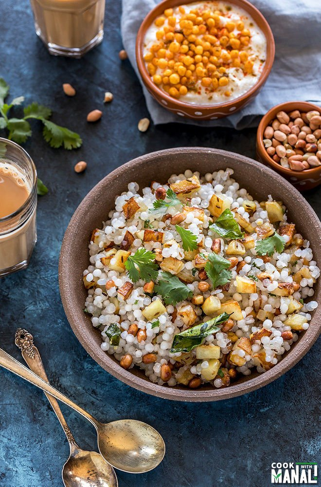 sabudana khichdi served in a brown bowl with a small bowl of yogurt in the back and a glass of chai on the side