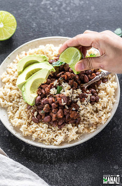 instant pot beans and brown rice served in a white place with sliced avocados