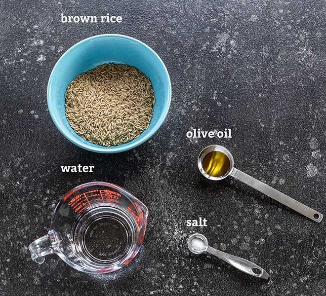 bowl of brown rice, spoon with oil and salt all placed on a board