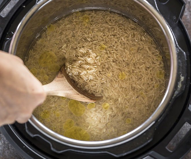 brown rice being stirred in the instant pot