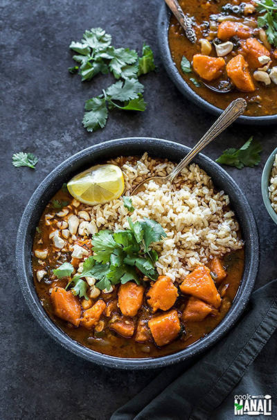 sweet potato curry in a black plate served with brown rice