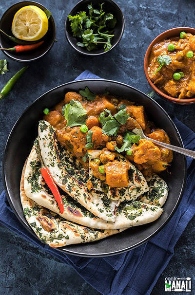 vegetable korma served in a black bowl with naan on the side
