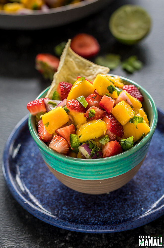 mango salsa in a blue bowl served with chips on the side