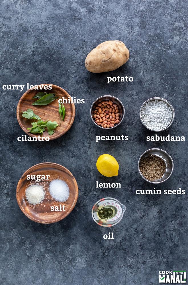 potato, lemon, bowl with peanuts, cumin seeds, sago pearls, lemon all arranged on a board