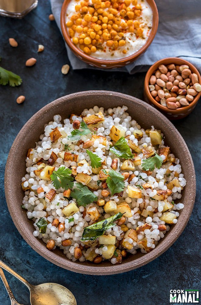 sabudana khichdi served in a brown bowl with a small bowl of yogurt in the back
