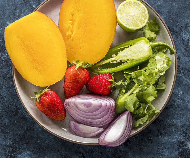 cut mangoes, strawberries, cut onion, cut lime and slice jalapeno in a plate