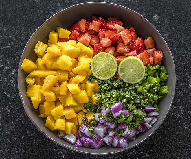 a large bowl with diced mangoes, strawberries, onion, jalapeño, cilantro and cut lime