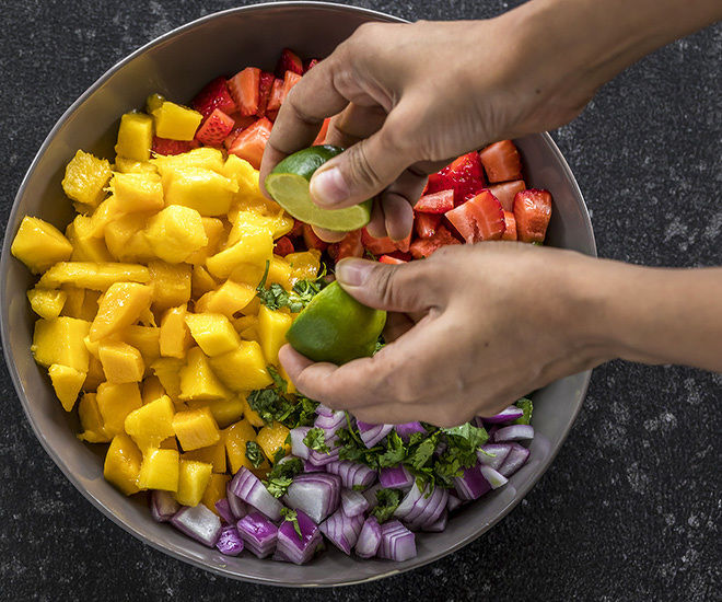 a pair of hand squeezing lime juice into a bowl of strawberry mango salsa