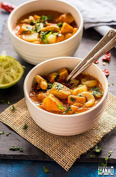 thai peanut tofu pineapple curry in a white bowl served with 2 spoons
