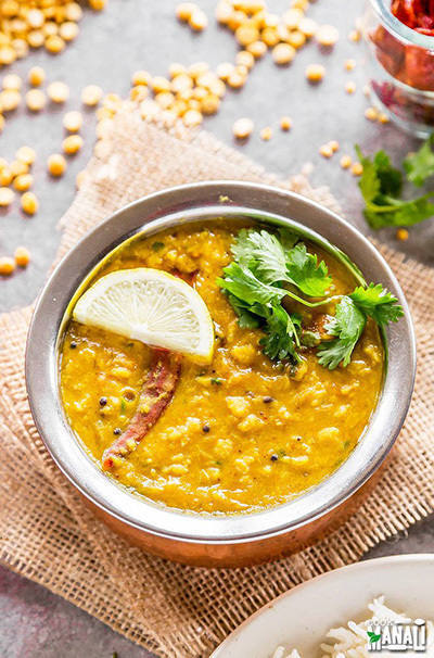 chana dal served in a round copper vessel garnish with cilantro