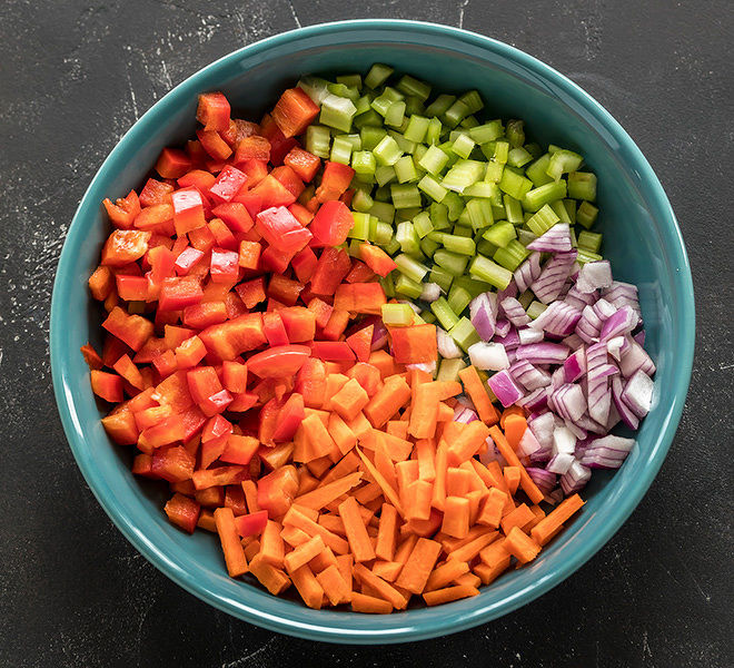 a blue bowl with chopped peppers, onion, carrots and celery