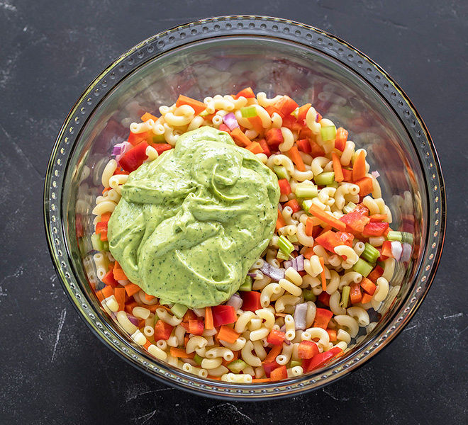 a bowl with macaroni, veggies and green avocado dressing