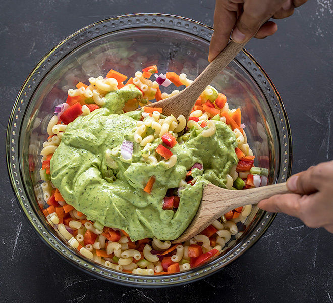 pair of hands tossing together vegan macaroni salad using a spatula