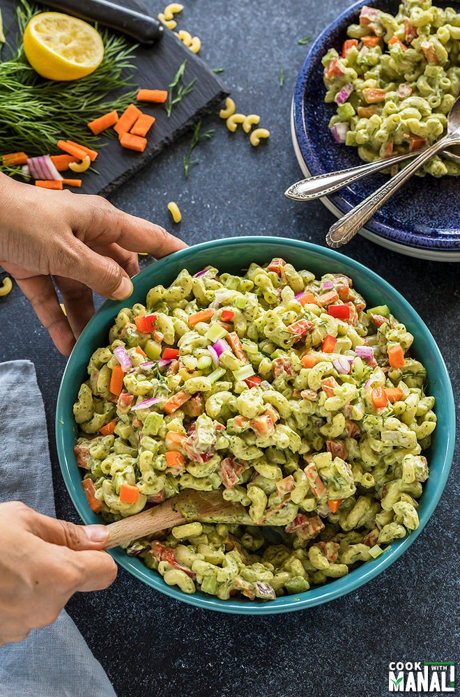 pair of hands mixing vegan macaroni salad with a spatula