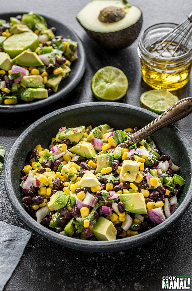 black bean and corn salad served in a small black bowl with a spoon