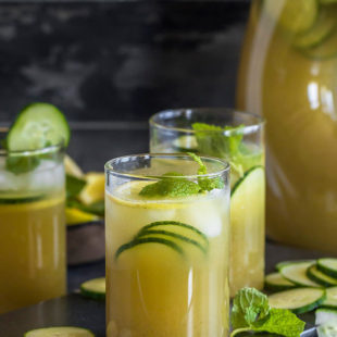 three glasses of a cucumber lemonade with a pitcher in the background