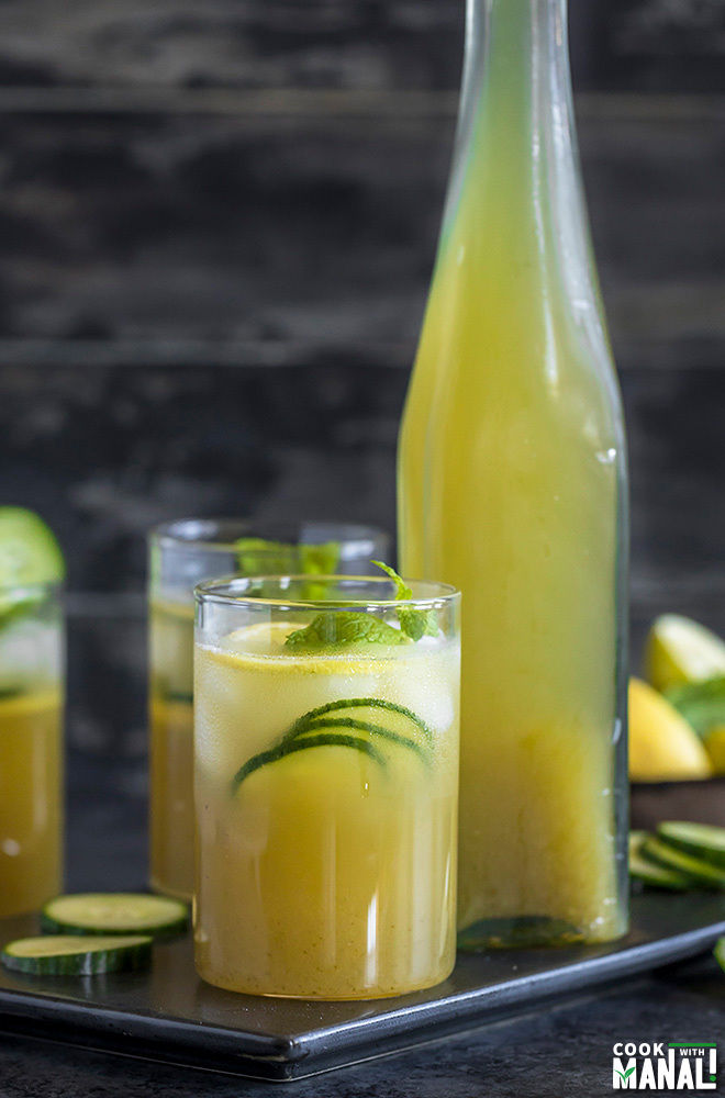 glasses of cucumber lemonade with a bottle of lemonade in the background
