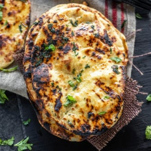 stack of naan garnished with cilantro and placed on a black board