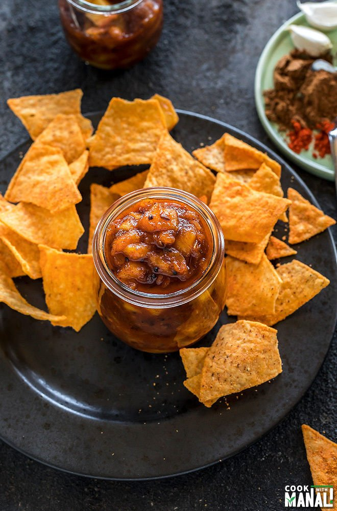 peach chutney in a small glass jar with chips on the side