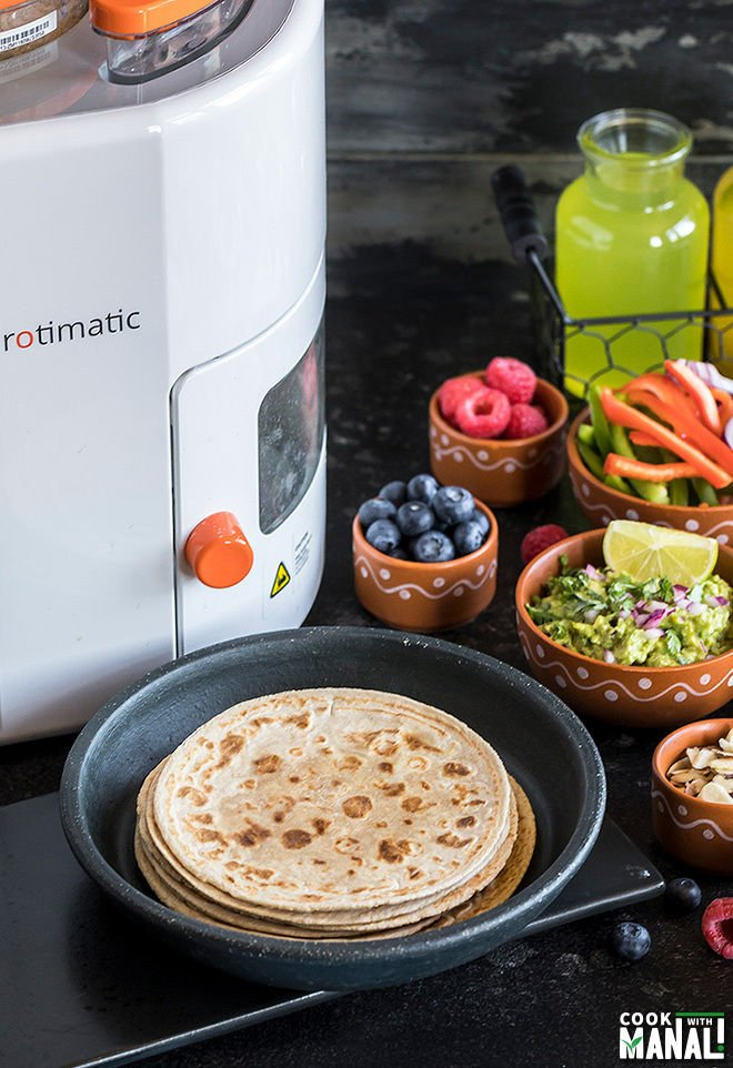 rotis with various toppings in bowls and rotimatic in the background