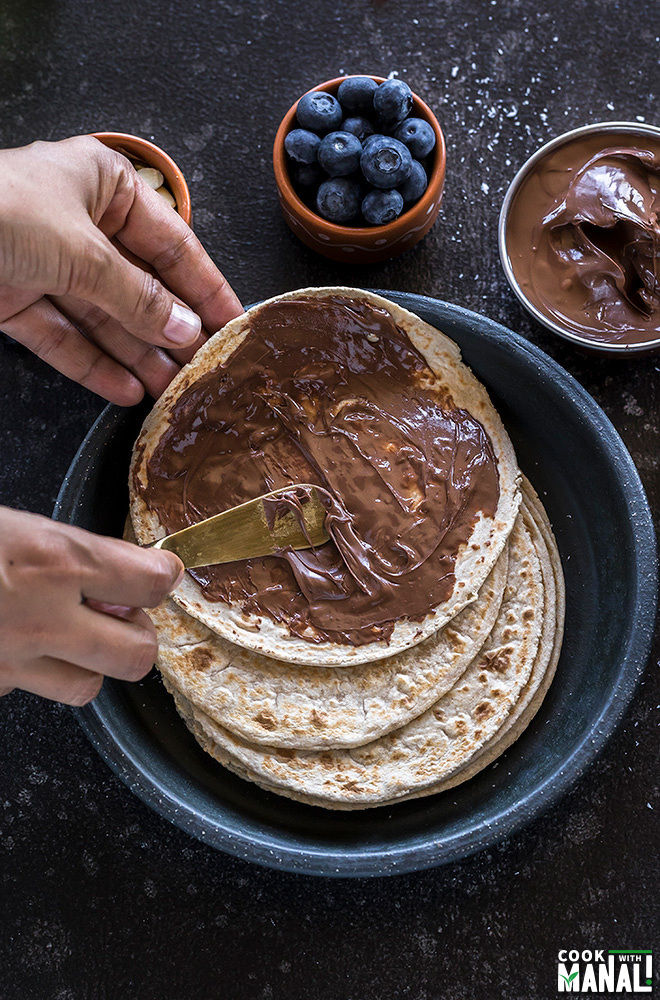 a pair of hands applying nutella on rotis