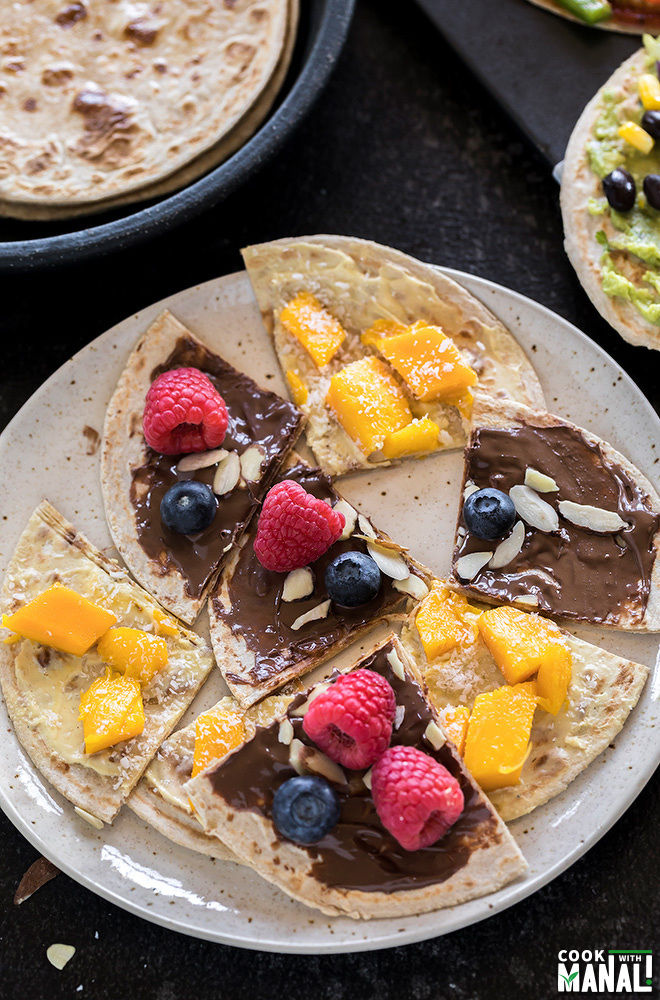rotis cut into triangles and topped with nutella, mango and berries