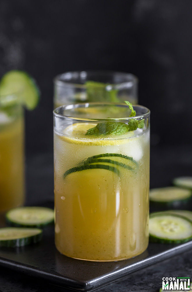a glass of cucumber lemonade with cucumber slices and mint leaves