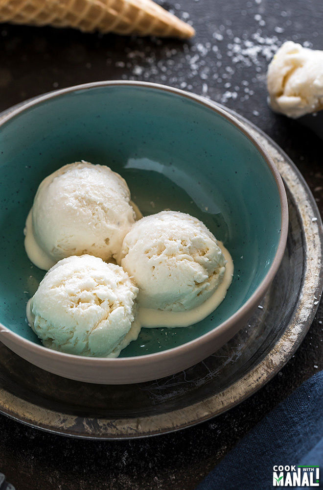 three scoops of tender coconut ice cream in a blue bowl