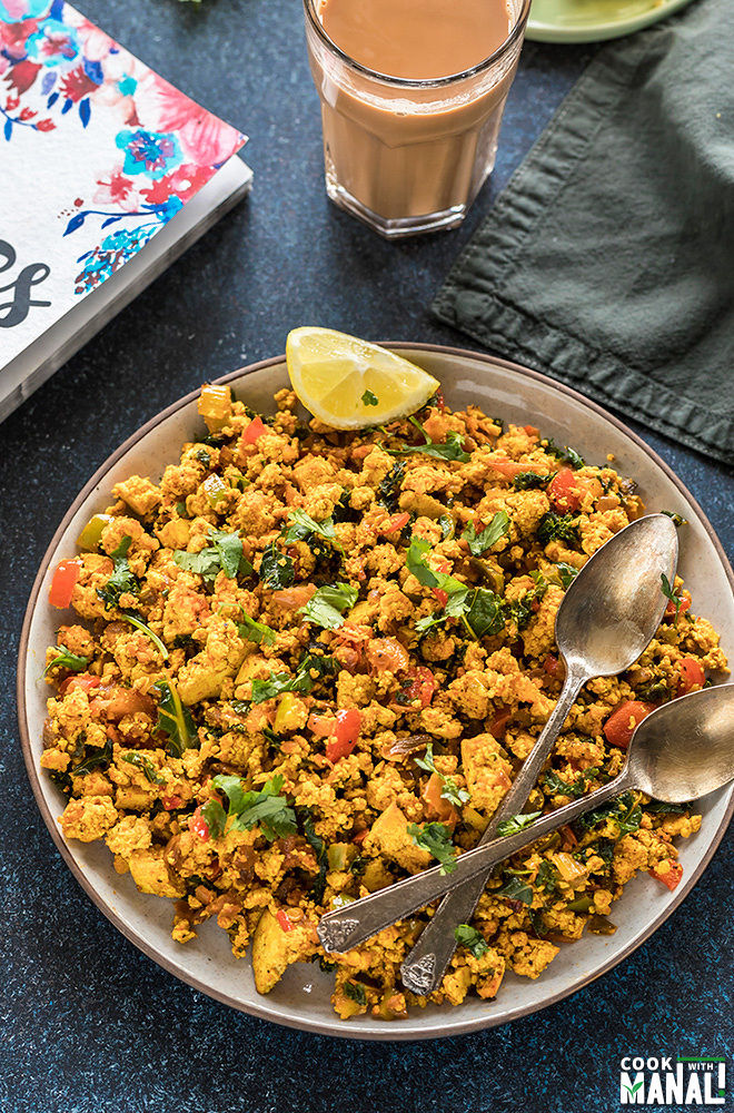 tofu scramble in a round plate with a glass of chai in the background