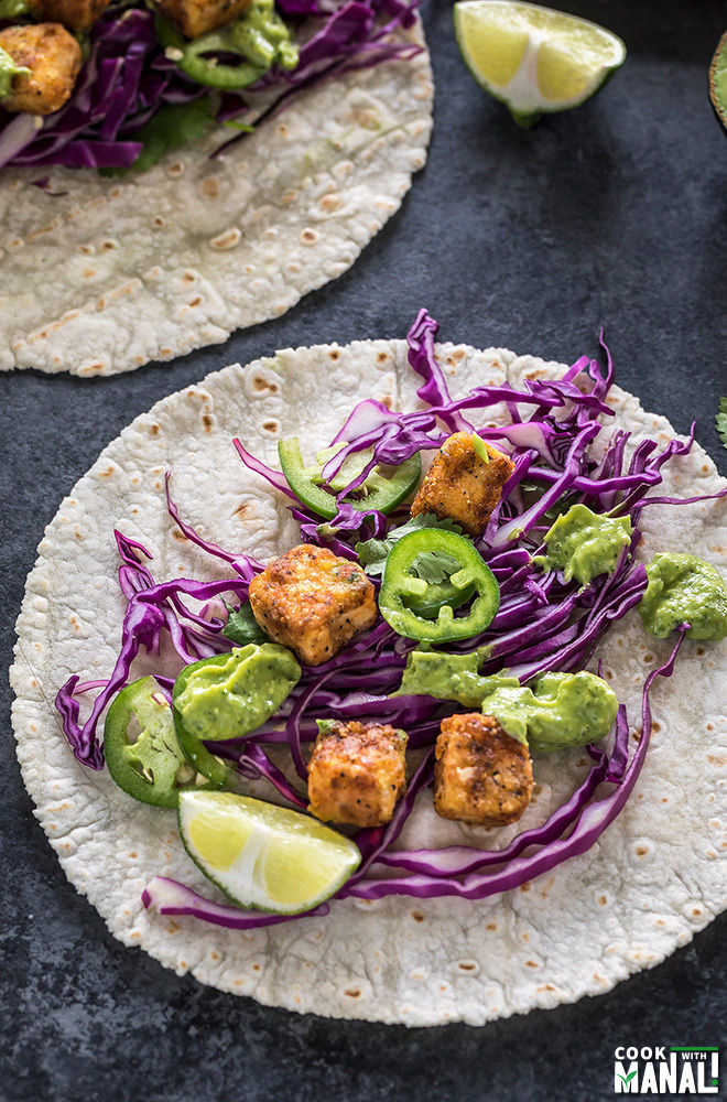 crispy tofu tacos topped with sliced jalapeno and shredded red cabbage