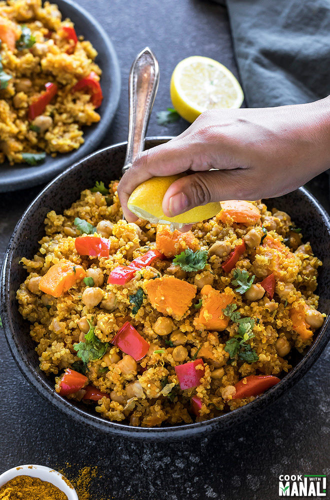 a pair of hands squeezing lemon juice into a bowl of sweet potato chickpea quinoa made in the Instant Pot