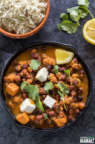 kala chana or black chickpeas curry served in a small cast iron skillet with a lemon and some cilantro on the side