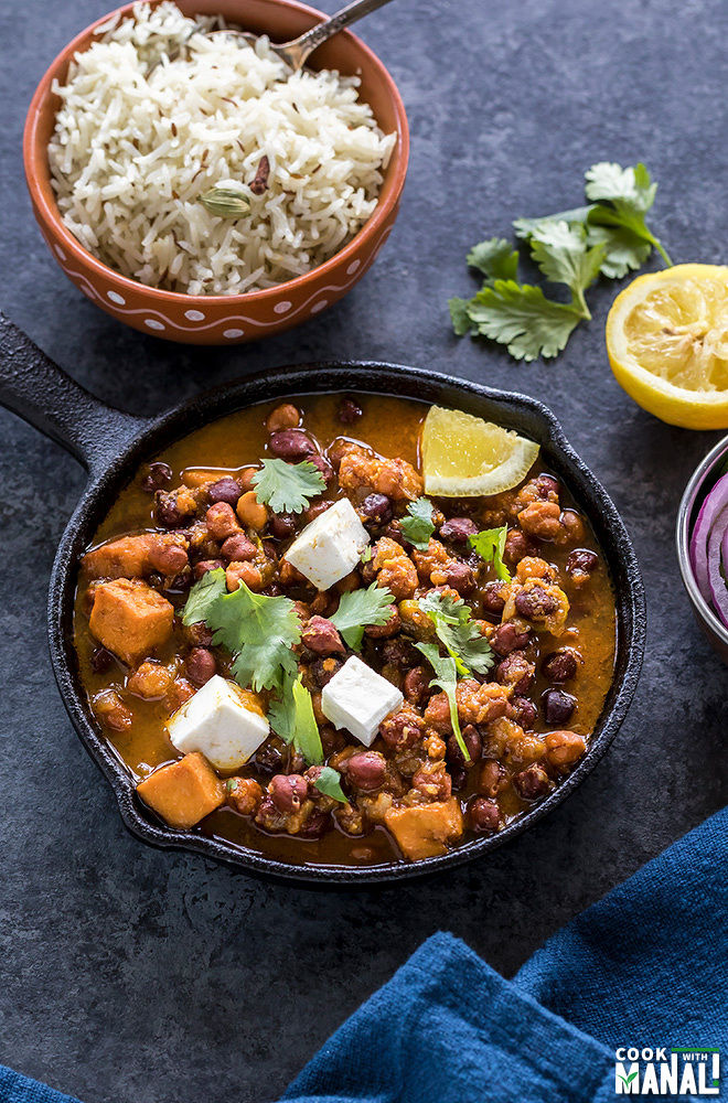 kala chana or black chickpeas curry served in a small cast iron skillet with a bowl of rice in the background and a squeezed lemon and some cilantro on the side