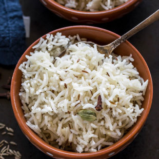 overhead shot of jeera rice served in a clay bowl with a spoon on the side